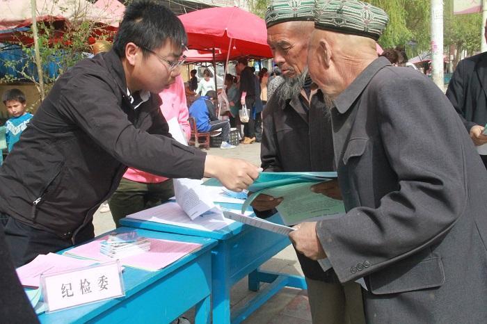 县纪委干部向群众介绍信访举报相关知识2.jpg